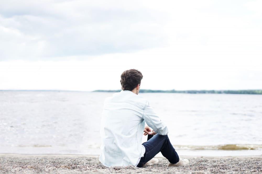 一人で海を眺める奥手な男性
