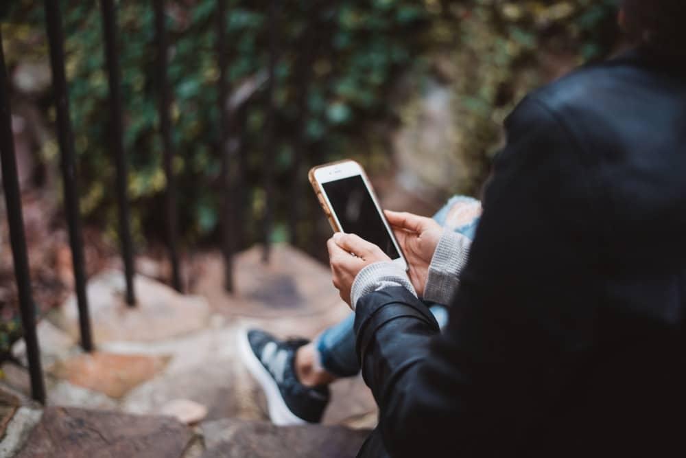 iPhone片手に電話をかけるかかけまいか悩む男性