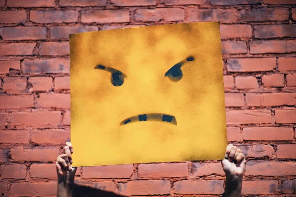 イライラしている男性心理を思い起こす怒っている顔が書かれた板