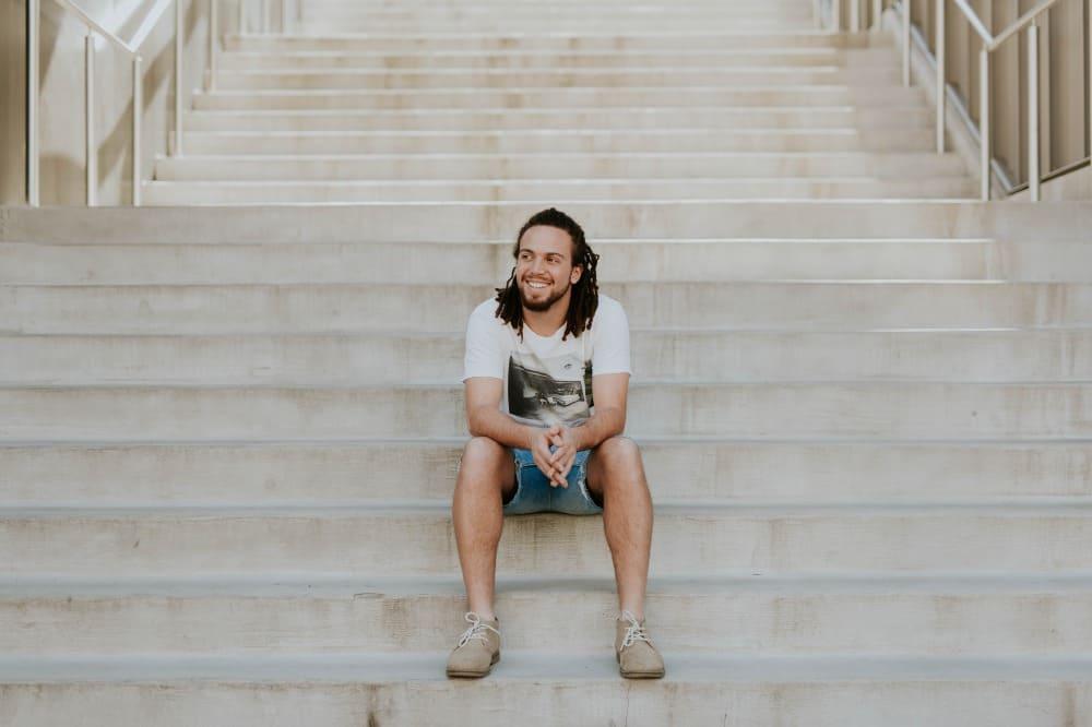 行為があるときの行動!?階段に座る笑顔の男性