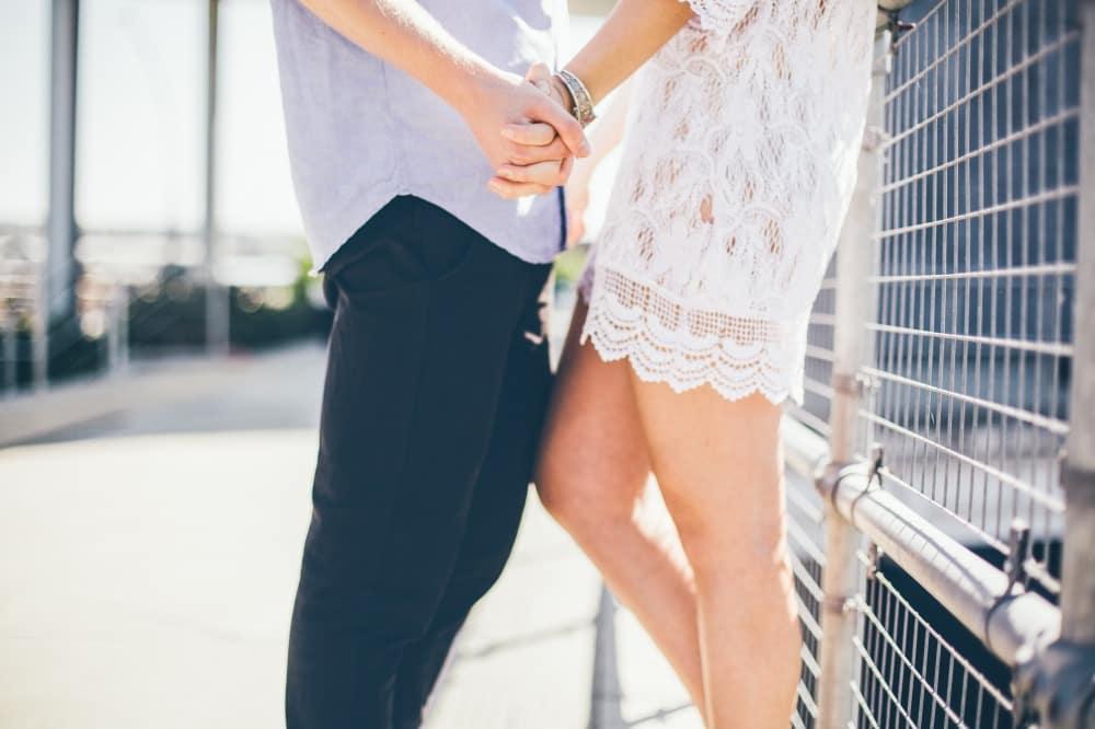 フェンスの近くで手をつなぎながら彼女に甘える彼氏