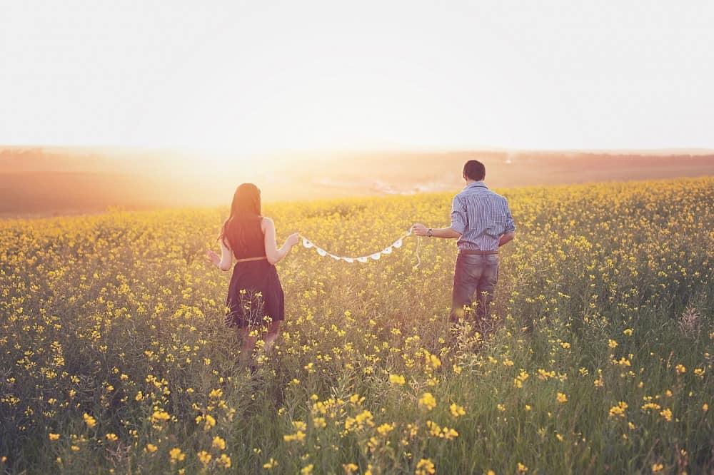 花畑で二人の距離感を確かめる男女