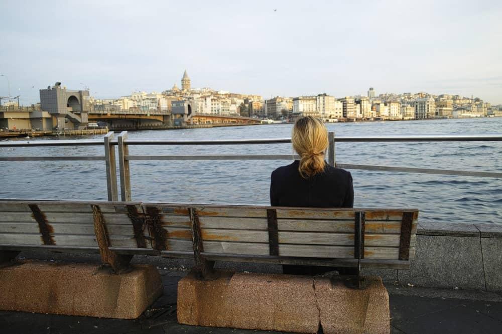 距離を置きたいといわれ寂しく一人で海を眺める女性
