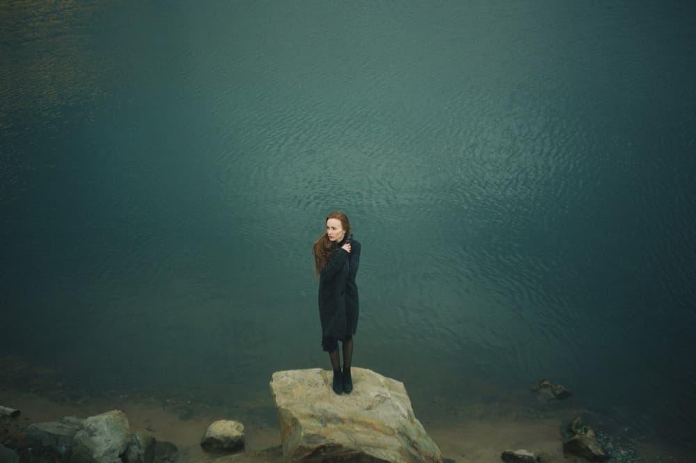 一人寂しく岩の上に立つ女性